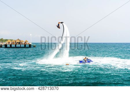 An Extreme Water Sport. A Guy Does Flip Tricks On A Water Flyboard. Extreme Vacation At The Sea.