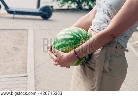 Female Hand Hold A Watermelon In Supermarket. The Buyer Chooses A Watermelon.