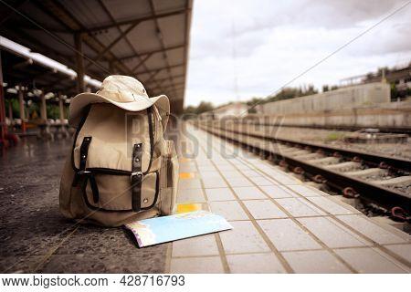 Travel Backpack, Hat, Traveler Map Near Railway At The Train Station. Vintage Travel Concept. Backgr
