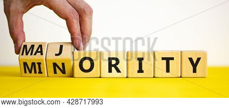 Minority Or Majority Symbol. Businessman Turns Wooden Cubes And Changes The Word 'minority' To 'majo