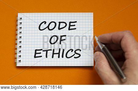 Code Of Conduct Symbol. Businessman Writing Words 'code Of Ethics' On White Note. Beautiful Orange B