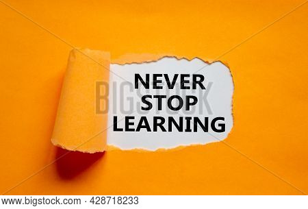 Never Stop Learning Symbol. Words 'never Stop Learning' Appearing Behind Torn Orange Paper. Beautifu