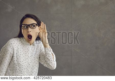 Woman With A Shocked Expression Holds Her Hand To Her Ear And Overhears The Conversation.