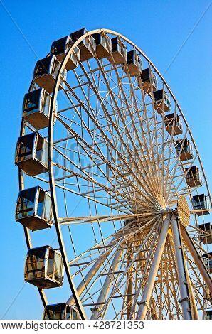 Ferris Wheel On The Background Of Blue Sky. Ferris Wheel In The Sunset.
