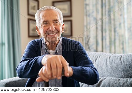 Portrait of smiling senior man holding walking stick sitting on sofa. Cheerful elderly man relaxing at home and holding a support stick with copy space. Happy senior with a big smile at nursing home.