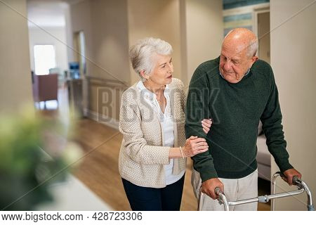 Elderly woman help her husband walking using walker in nursing home. Senior woman helping disabled man with walking frame. Lovely wife holding hands of old husband in care centre.