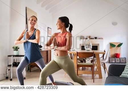 Mature woman practicing yoga at home with mixed race friend. Beautiful sporty indian woman with female friend in yoga position of the warrior at home. Two middle aged lady exercising at home, lockdown