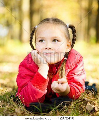 Portrait of a cute little girl in autumn park