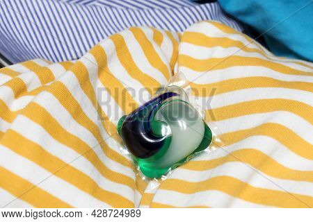 Detergent Pods A Means For Washing And Removing Stains Lies On A Pile Of Laundry. The Concept Of Cle