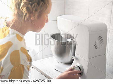 Teenager Girl Looking At Planetary Mixer Bowl With Whipping Cream. Side View Of A Girl Making Whippe