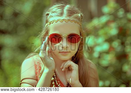 Portrait of a cute girl child dressed in hippie style posing outdoor. Romantic hippie style.