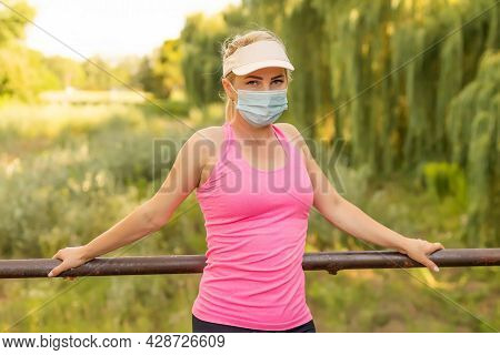 Pandemic Coronavirus Covid-19 A Woman In A Meadow In A Sports Outfit Wearing A Protective Mask In Ca