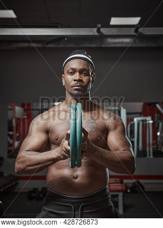 Handsome Muscular Athletic African American Man Exercising With Weight Plates. Training In Gym