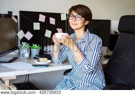 Woman In Glasses Drinking Coffee On The Break To Relax During Work On Her Home Office Workplace. Sat