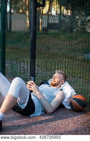 Basketball Player Athletic Male Lying Relaxing With Phone After Workout Outdoors On Sports Court