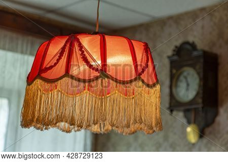 Vintage Lampshade Made Of Red Fabric With Fringes As An Element Of The Decor Of The Interior Of The