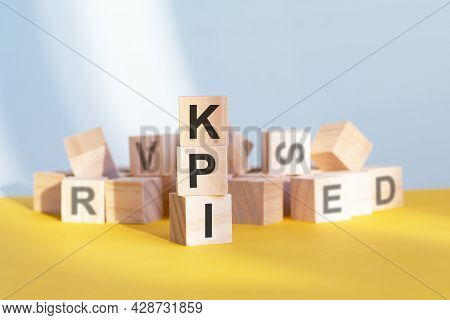 Wooden Cubes With Letters Kpi Arranged In A Vertical Pyramid, Yellow Background