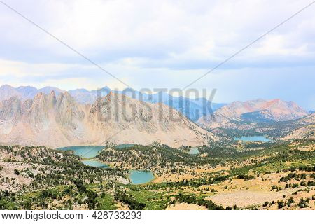 Alpine Lakes And Pine Forests On A High Altitude Plateau Surrounded By Rugged Mountain Ridges Above