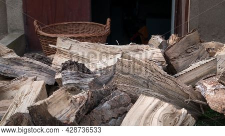 Chopped Firewood, Logs, Piled On A Pile. They Are Placed In Baskets And Stored In The Basement. Wint