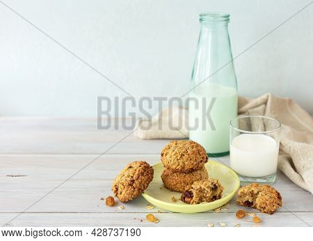 Oatmeal Cookies With Raisins, Glass And Bottle Of Milk On Wooden Background With Napkin. Concept: He
