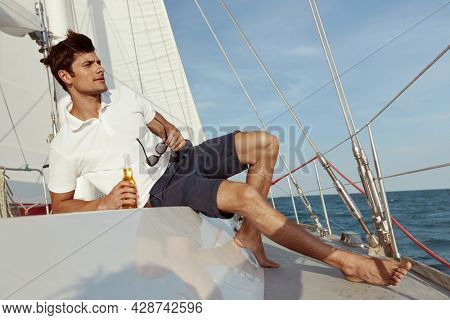European young man lying and drinking beer on his yacht in sea or ocean. Luxury boat. Focused guy wear shorts, shirt and hold glasses. Concept of sailing vacation or tourism. Summertime. Sunny daytime