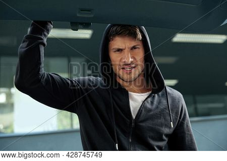 Angry european robber looking in car trunk. View from auto trunk with human victim. Male bearded bandit wear black hoodie. Concept of kidnapping. City daytime