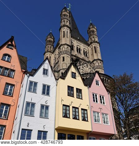 Small Colorful Houses In Front Of The Church Of Great St. Martin In Cologne's Old Town