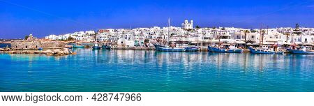Greece travel. Cyclades, Paros island. Charming fishing village Naousa. view of old port with  boats and street taverns by the sea.