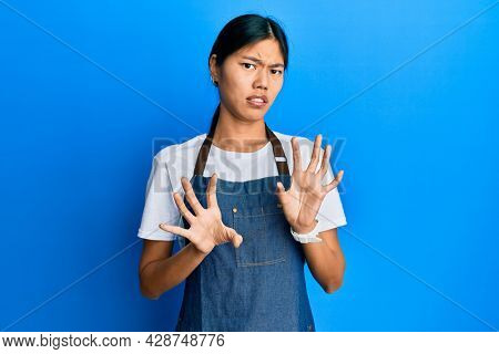Young chinese woman wearing waiter apron disgusted expression, displeased and fearful doing disgust face because aversion reaction. with hands raised