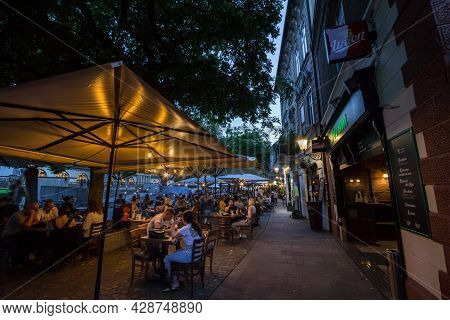 Ljubljana, Slovenia - June 16, 2021: Selective Blur On A Packed Patio Of A Cafe Restaurant With Peop