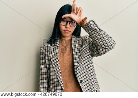 Young chinese woman wearing business style and glasses making fun of people with fingers on forehead doing loser gesture mocking and insulting.