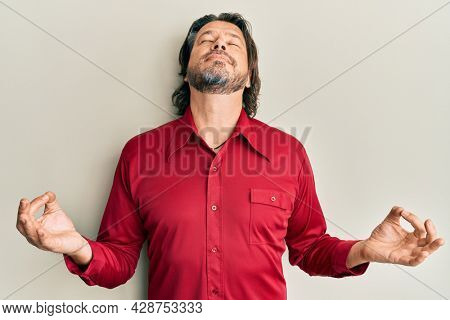 Middle age handsome man wearing casual clothes relax and smiling with eyes closed doing meditation gesture with fingers. yoga concept.