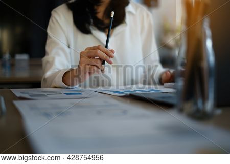Close Up Business Woman Hand Holding Pen And Pointing At Financial Paperwork With Financial Paperwor
