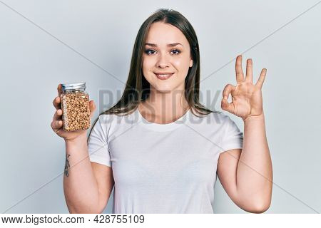 Young hispanic girl holding lentils bowl doing ok sign with fingers, smiling friendly gesturing excellent symbol