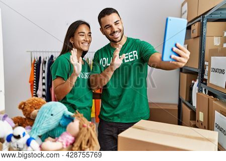 Â¡Young latin volunteer couple having video call using touchpad working at charity center.