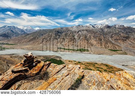 View of Spiti valley and Spiti river in Himalayas with stone cairn . Spiti valley, Himachal Pradesh, India