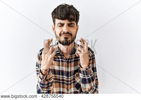Hispanic man with beard standing over isolated background gesturing finger crossed smiling with hope and eyes closed. luck and superstitious concept.