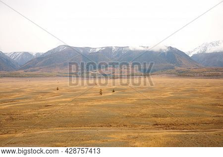 Ribbed Autumn Steppe At The Foot Of A Mountain Range With Snow-capped Peaks.