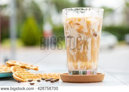 Iced Caramel Latte Coffee In A Tall Glass With Caramel Syrup