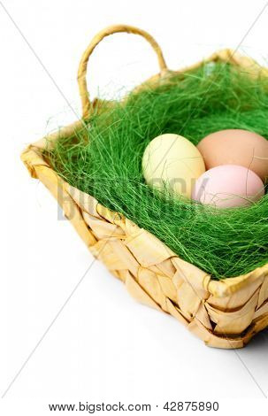 Colored easter eggs are in braided basket with sisal green fibre, isolated on white