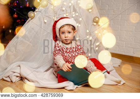 Happy Little Boy Is Looking At Family Album Or Reading A Book While Sitting Under The Christmas Tree
