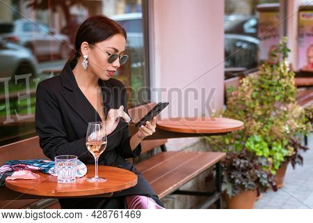 A Successful Young Woman Of Caucasian Appearance In A Black Suit Sits In A Cafe With A Phone In Her