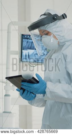 Professional Stomatologists Using Digital Tablet In Dental Cabinet At Clinic. Dentist And Assistant