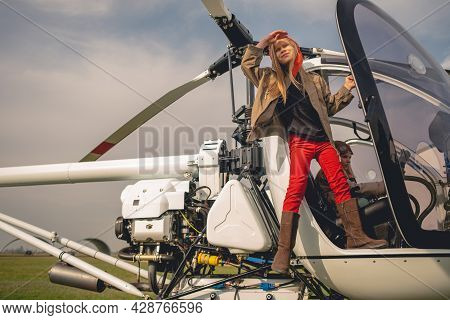 Full Length Portrait Of Tween Girl Looking At Sky From Open Cockpit Of Helicopter