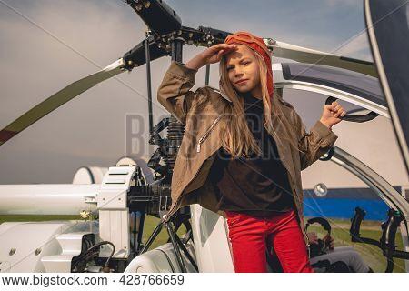 Serious Preteen Girl In Aviator Hat In Doorway Of Open Helicopter
