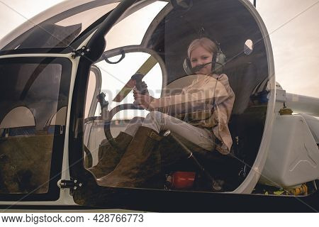 View Through Glass Of Cockpit Of Tween Girl Imitating Helicopter Control