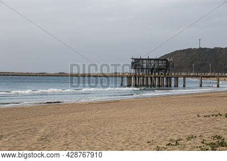 Empty Beach And Pier With Bluff In Background