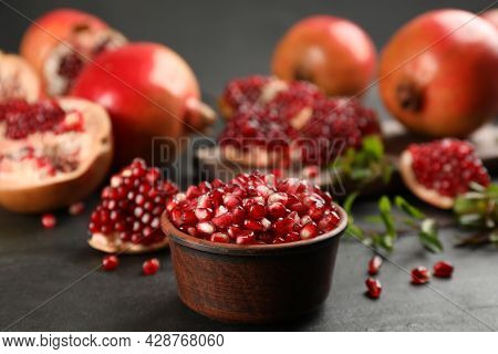 Delicious Ripe Pomegranate Kernels In Bowl On Black Table