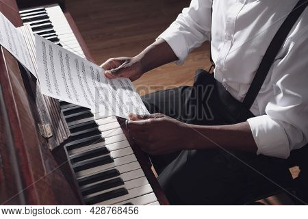 African-american Man With Note Sheets At Piano Indoors, Closeup. Talented Musician