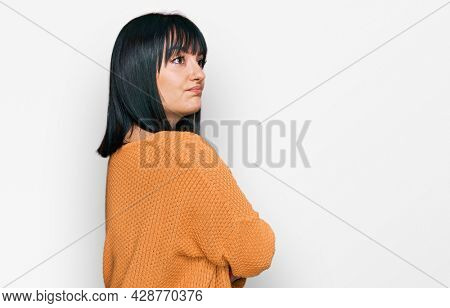 Young hispanic woman wearing casual clothes looking to the side with arms crossed convinced and confident